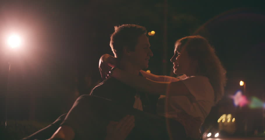 Loving young couple out in the city at night on a date with the guy spinning his girlfriend in Slow Motion under the street lights