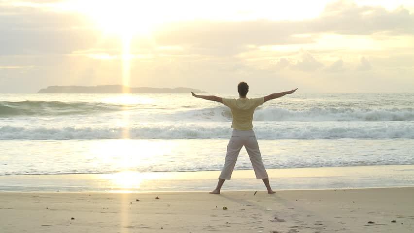 HD 1080i: Young woman doing yoga on the beach at sunrise in Bombinhas - Brazil. Tripod.