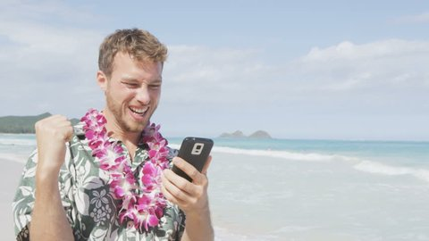 Celebrating man winning on smart phone app on Hawaii beach. Cheering winner in celebration over good news or success in online game app. Young man on vacation travel in Hawaiian clothing.