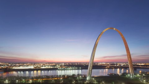 4K Time lapse aerial view St Louis Gateway Arch at sunrise with boat traffic on the river and red colored clouds