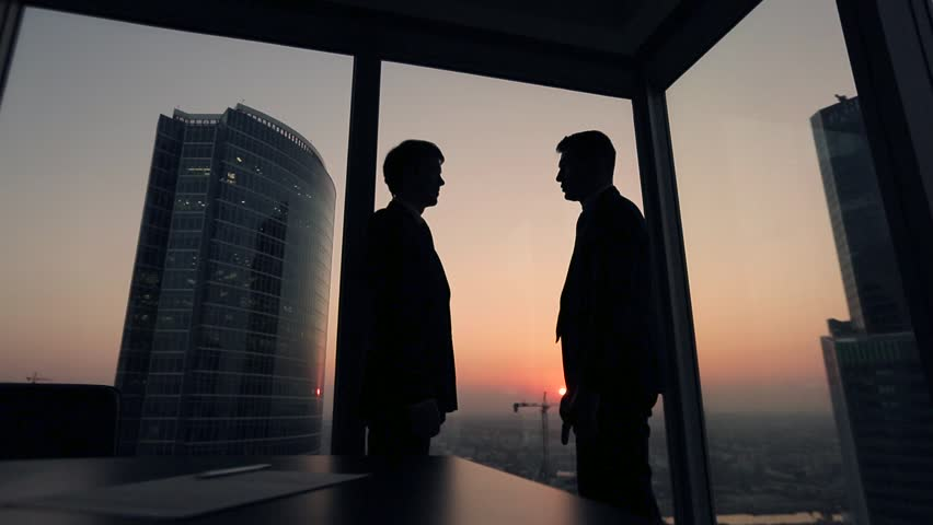 Two businessmen partners handshake in office. Silhouettes at sunset outside the window. | Shutterstock HD Video #12411749
