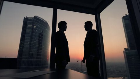 Two businessmen partners handshake in office. Silhouettes at sunset outside the window.