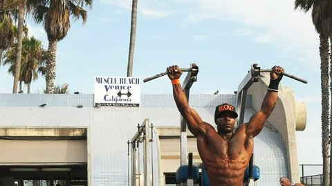 LOS ANGELES, CALIFORNIA, USA - AUGUST 25, 2015: close up of a bodybuilder performing slow controlled pullups while exercising at venice beach, los angeles.