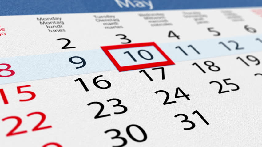 Date pointer moving over pasteboard calendar, close up