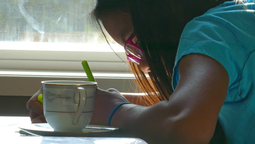 A cute 13 year old Asian girl spends time drawing on the kitchen table while enjoying a sunbeam. | Shutterstock HD Video #12428258