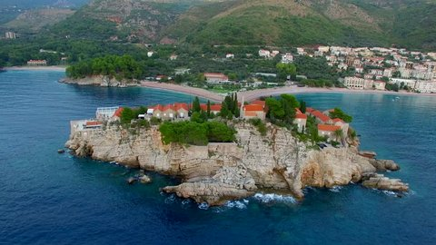 A helicopter flight over the island of Sveti Stefan in Montenegro. Aerial photography, video from a height, the height of bird flight. Flying over the sea, the coast and the Balkans