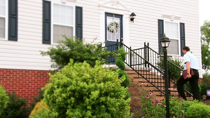 A door to door salesman walks up to a house and knocks on the door.