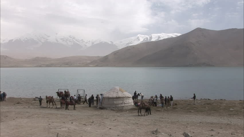 Xinjiang, China - October 2007: Tourists, camels & riders on horses near a traditional Kyrgyz hut with Karakuli Lake and Pamir Mountains in background in Xinjiang, Western China. - HD stock video clip