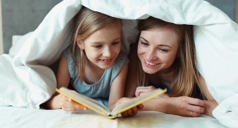 Closeup portrait family mother and daughter reading book under the blanket and laughing