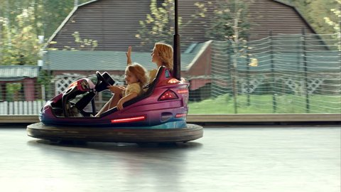Happy mother with her daughter drive on bumper cars in Amusement park. Shot on BMCC RAW with high dynamic range. You can use it e.g in your video, documentalistic, reporting, family, music video