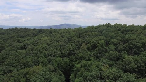 Aerial shot rising over the treetops revealing the Appalachian Mountain Range on a bright day.