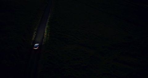4K Car Driving at Night on Winding Country Road in the Hills. Aerial View. Headlights.