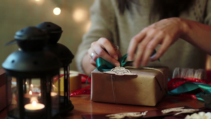 Young Woman Wrapping Christmas Gifts With Brown Paper At Home