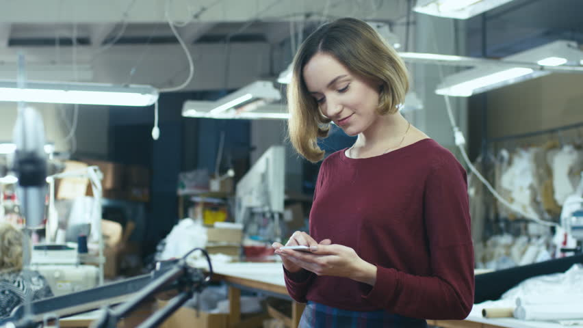 Young woman is standing in a clothing factory and using a smartphone while employees work in the background. Shot on RED Cinema Camera in 4K (UHD)