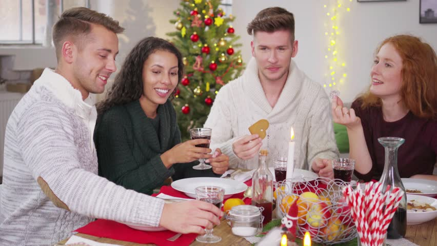 Four Young Adults Celebrating Christmas With A Dinner At Home