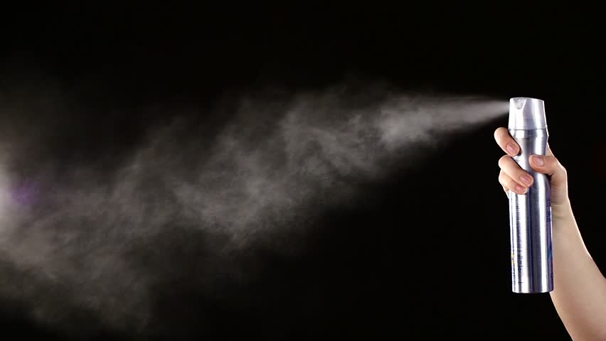 Spray bottle drops for hairstyle on black background, slow motion