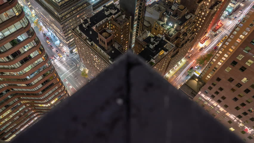 Motion controlled tilt / panning time lapse unique view from a rooftop in midtown Manhattan at night showing traffic and panning up to the skyline. (New York, NY - Oct 2015)