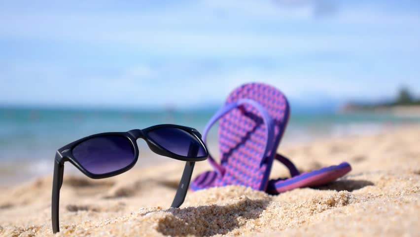 07593e23ab92 Summer Vacation Concept - Flipflops and Sunglasses on Sandy Ocean Beach.  Closeup. HD