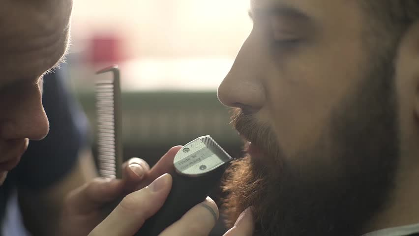 Hairstyling process. Close-up of a barber drying hair of a young bearded man