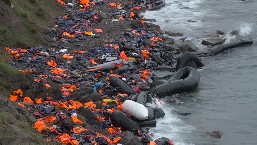 Destroyed rafts and abandoned life jackets line the beaches of Lesbos, Greece as thousands of refugees pour into Europe.  | Shutterstock HD Video #12590708