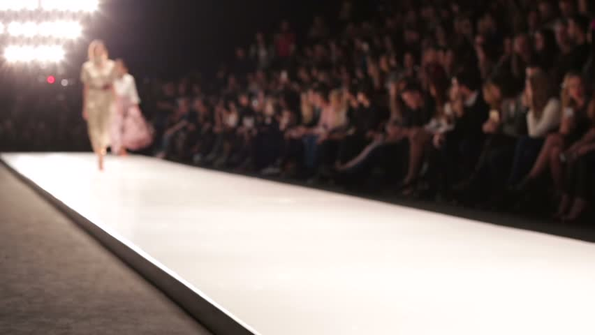 Out of focus background, models walk the runway during fashion show. | Shutterstock HD Video #12626378