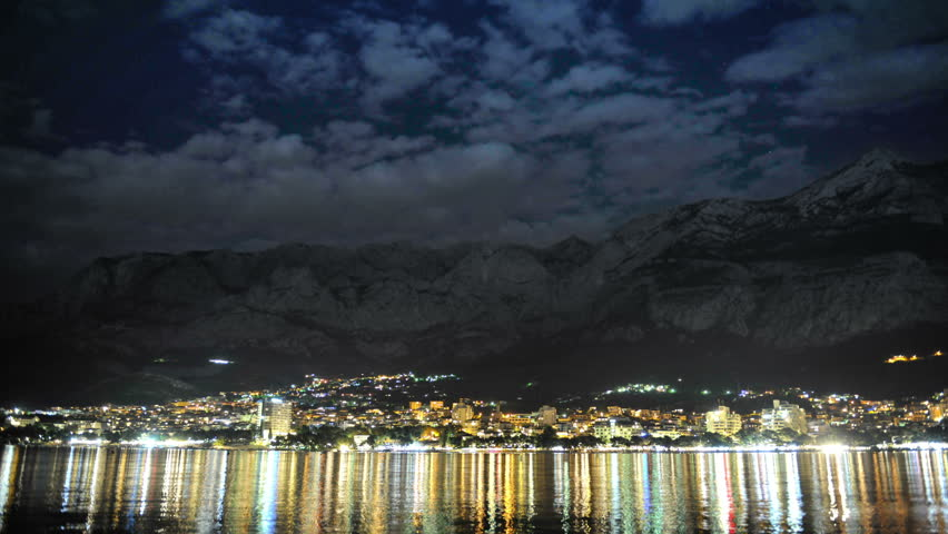 Cinemagraph, clouds traveling over the frozen sea, cityscape at night, Makarska summer 2015. Croatia. Beautiful reflections of lights on the sea | Shutterstock HD Video #12644762