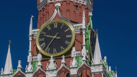 Moscow Kremlin, Red Square. Spasskaya Savior's clock tower timelapse hyperlapse decorated by the red ruby star on the top of it. Blue sky background. UNESCO World Heritage Site.