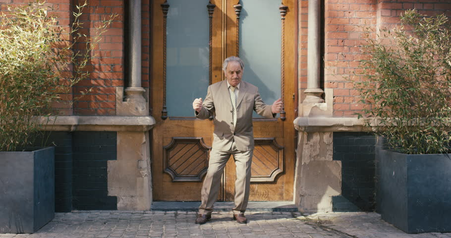 Happy elderly dancer man wearing suit in front of apartment funky street dancing freestyle in the city | Shutterstock HD Video #12658718