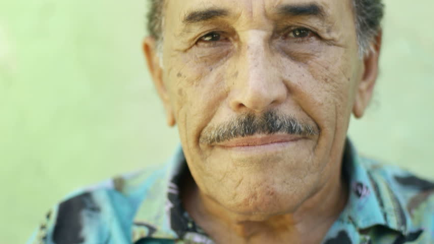 Portrait of senior hispanic man with mustache looking at camera against green wall and smiling. Elderly, old people and feelings