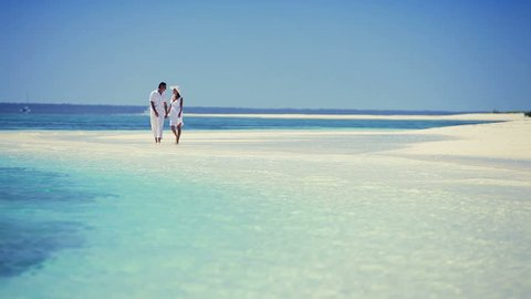Attractive caucasian couple walking through the shallows of  a secluded tropical island