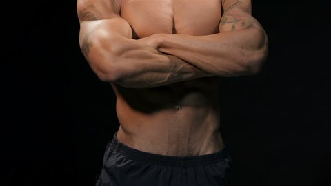 Close up man with arms crossed on his chest showing his muscular torso. Muscular man bodybuilder. Man posing on a black background, shows his muscles. Bodybuilding, posing, black background, muscles -