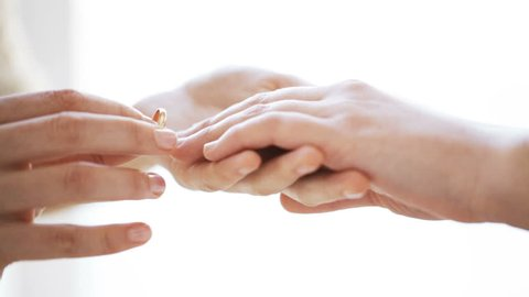 people, homosexuality, gay, same-sex marriage and love concept - close up of lesbian couple hands putting wedding ring on
