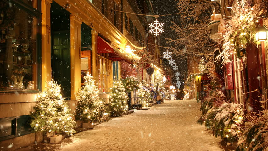 Snow is falling on deserted street decorated for Christmas.