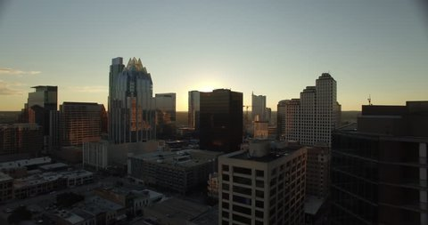 The camera starts wide as it approaches the Austin, Texas skyline.  It sweeps left to right and gains altitude to show the sun setting in the distance while it simultaneously silhouettes the city.