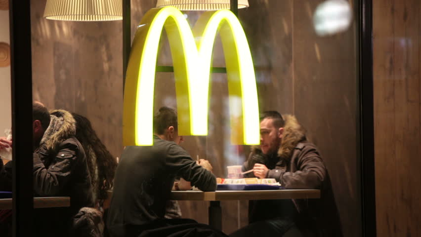 POLAND, KRAKOW - JANUARY 1, 2015: People sit at little tables at McDonald's restaurant. McDonald\x92s Corporation- American corporation, till 2010 world's largest network of restaurants of a fast food