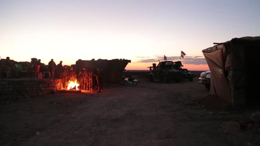 Kurdistan November 2015: Soldiers Standing Around Campfire with Kurdistan Flag in Sunset
