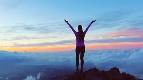Reaching The Top. Happy successful fitness woman raising arms to the sky at sunset. Success