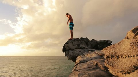 Young Man Jumps off Cliff Into Water. Summer Extreme Sports Outdoor Lifestyle. Cliff Jumping at Sunset.