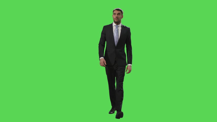 Businessman in a suit is walking on a mock-up green screen in the background. Shot on RED Cinema Camera in 4K (UHD).