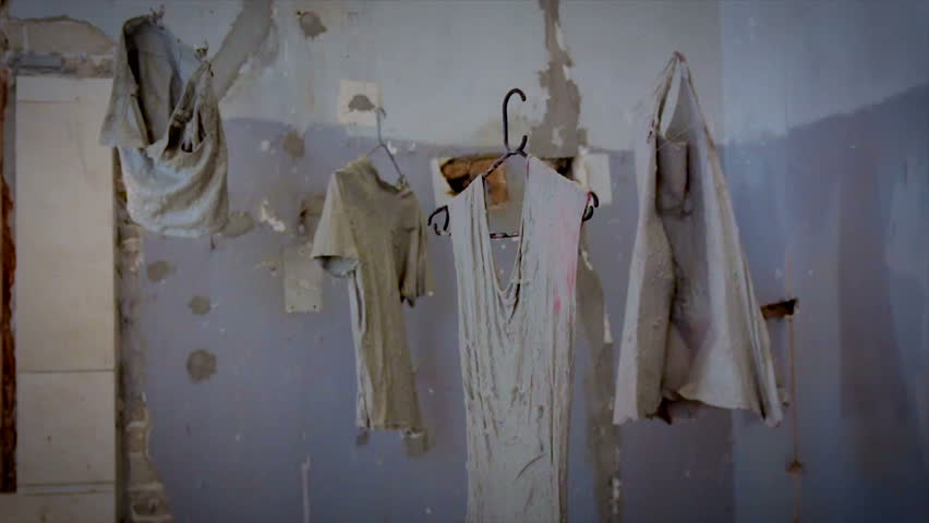 Clothes coated with concrete are hanging in the air - abstract style grunge art. The clothes hanging in the air, spinning in place, and look like corpses. | Shutterstock HD Video #12900278