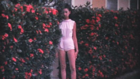 PENSACOLA, FLORIDA, JUNE 1969: An attractive young college aged girl poses in front of a hedge while on holidays in the summer of 1969 in Florida.