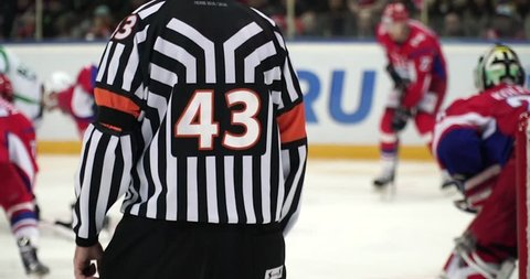 Hockey referee hold a puck in his palm. Slow motion