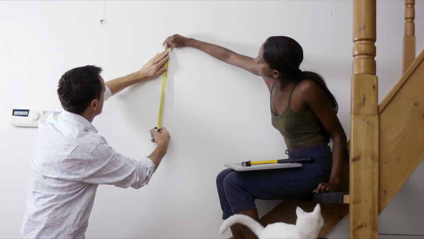 Do it yourself, interracial couple measuring wall to hang picture at home. People, man, woman, husband, wife, home decor and improvement