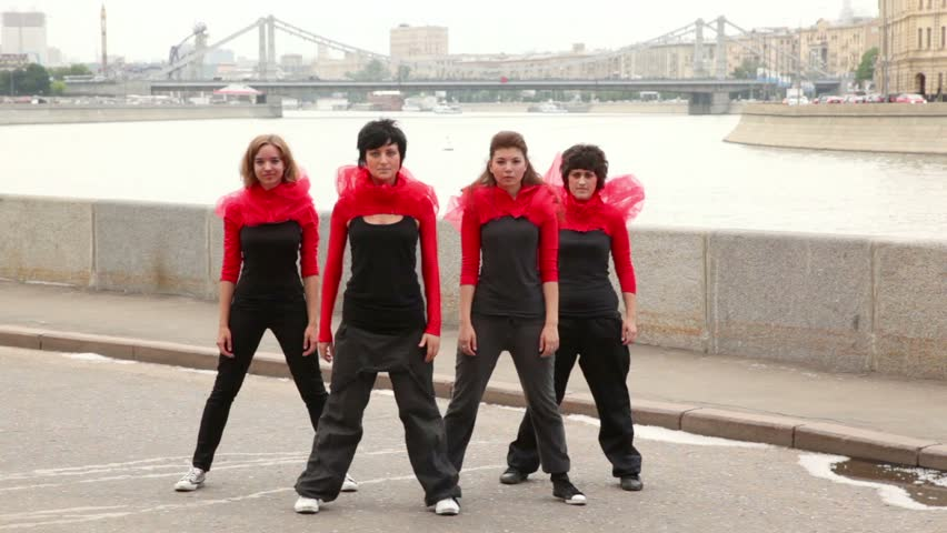 Four girls dance synchronously on quay, then turn around, at background of city traffic on bridge in Moscow