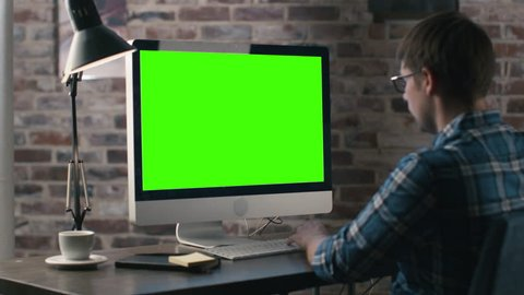 Young man is working on a computer with a mock-up green screen. Shot on RED Cinema Camera in 4K (UHD).