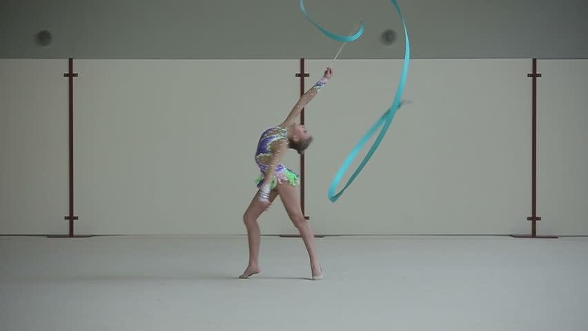 Rhythmic gymnastics: Girl training a gymnastics exercise with a ribbon. Slow motion