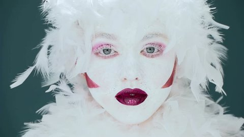 portrait of a woman mime or a clown and bodypainting white with red lips and red eyes
