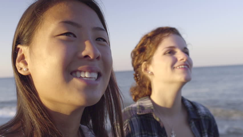 Closeup Of Multiethnic Teen Girls Looking Up With Wonder At Sky, On The Beach
