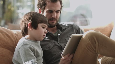 Father and son on the couch using digital tablet