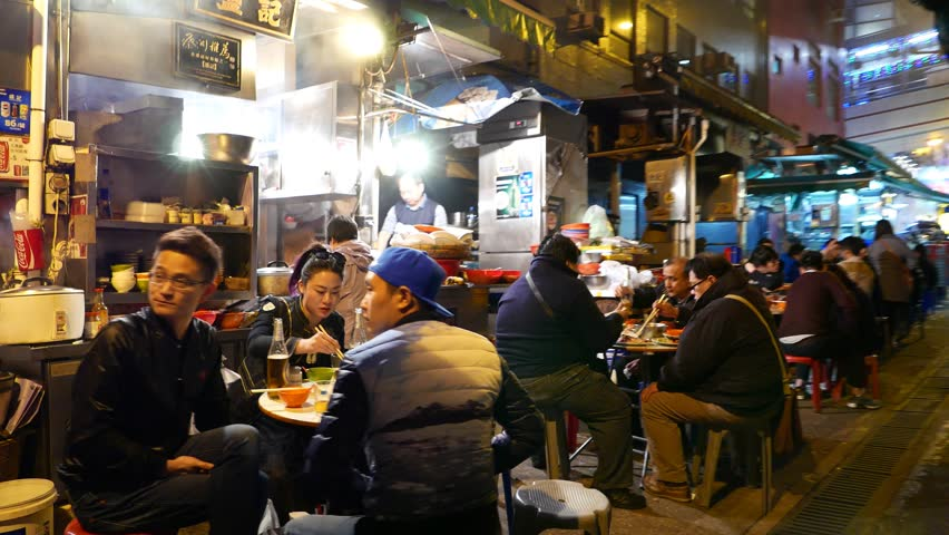 HONG KONG - FEBRUARY 10, 2015: Truly authentic chinese fast-food street in night, with sound. While all restaurants on first level of building closed in night time, many food-kitchen booth
